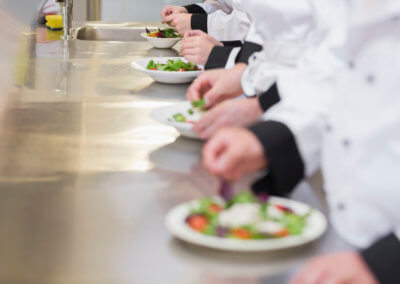 Chef's preparings salads in a row on a counter