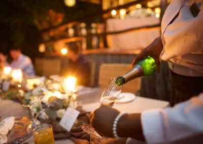 Pouring of Champagne at Outdoor Wedding Celebration by African waitress