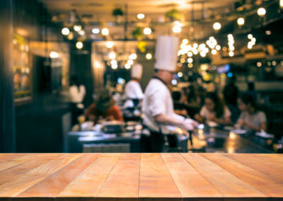 Wood table top with blur chef cooking in bar restaurant